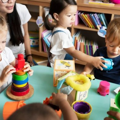 nursery-children-playing-with-teacher-classroom_53876-82775