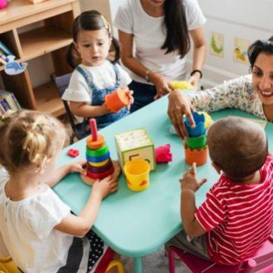 nursery-children-playing-with-teacher-classroom_53876-84223